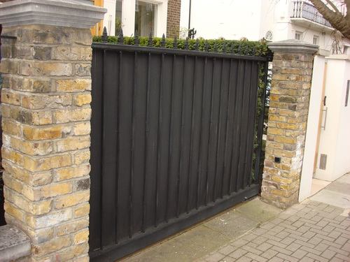Another sheeted wrought iron gate with metal sheeting for security and privacy, and decorations on the top