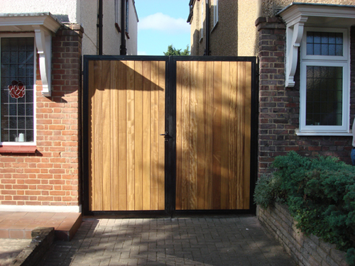 A pair of wooden side gates in wrought iron frame for extra security.